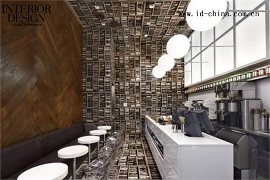 """进入酒吧,人们会注意到房间均偏向一侧右转。这种错觉是因为设计师用大量墙纸装饰,不仅是墙面,墙纸还一直延伸到天花板和地板。这使咖啡吧主题""""拿走""""显露无疑,拿走一杯咖啡就像从图书馆里拿一本书一样简单。玻璃柜台影射着墙纸,并照亮整个空间。设计师采用简约风格的家具,却又不失时尚,内部设计创新而原始,令人舒适放松。"""