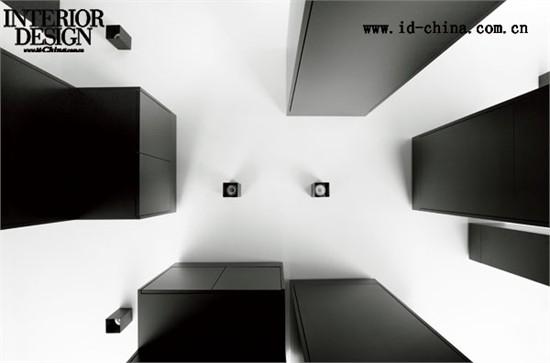 设计阶段模型,可以清晰地看到功能盒的分布关系  老公寓遗留下来的壁炉,砖砌的纹路形成了美丽的装饰       白色的墙壁与黑色的墙壁,使得空间看起来或许过于单调——用作书架的家具模块有效地调节了这一点,主人的书籍有秩序地排列在书架里,色彩缤纷的书籍成为了房间内最好的色彩装饰。壁炉边的画与绿植,则使得这个单色的空间生机勃勃。设计师精巧的心思不仅体现于此——厨房水槽的灯具被设计为淡绿色,温和清澈的光芒既吻合了水的特质也调节了这部分空间的气氛。而在卧室里,花纹清
