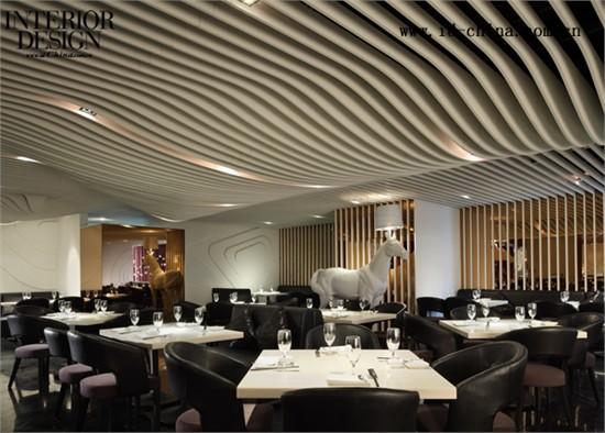 """餐厅用餐空间分割成三个区域, 两个元素。一是白色曲线板, 板子之间的镜子为了强调太极""""阴""""与""""虚""""的女性概念,曲线的构成来自麻辣诱惑品牌LOGO 。设计师运用现代的手法演绎品牌女性曲线形象的基本结构, 墙与顶面大量的曲线强调了人体美学,横面的曲线来自纵向曲线的迭层,这些变化的界面将内部空间进行了重新定义,顺应了空间跨度的力学需要,并传递了某种微妙的动感。"""