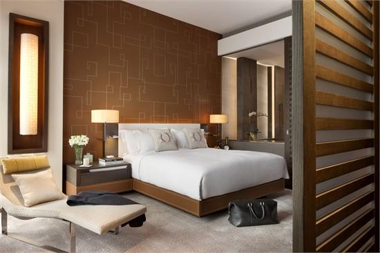 """朗廷还是皇室御用酒店,酒店招牌色粉色点缀于各细节。当开始设计酒店前台时,Peter的灵感来源于森林和透过树木的光。他把这种景象复制在柱子的设计上,前台仿佛藏于树丛的枝干中。设计师强调:""""我的目标是将上海内外元素充分融合。想到上海时,我联想到的是充满醉人魅力、和那些已逝去的年代的色彩。我努力将这些情绪和令人怀念的色彩溶入酒店的主题色中;对我而言,酒店在为他们的客人创造一种体验,我希望将这些元素和时尚同时融入设计。""""在酒店大堂的设计中,借鉴了舞台幕前的风格,凯旋餐厅拥有三层高的中庭"""