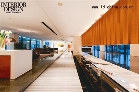 进入大厅,首先看到的是一组上下悬空且贯穿整个空间的木质格栅,将一层空间自然地划分为前台等候区和洽谈区,而位于2-4层的办公区域和过往的人群也被隐藏起来,从而产生了一道内部连廊,减少了公共空间里人流的相互干扰。木格栅是这个设计简洁洗练的空间中最具视觉冲击力的元素,但是设计师并未采取通常的设计做法,而是将格栅整体悬空,并在其下地面安装了射灯,使来客透过木质隔栅可以隐约地看到建筑物后面的中庭绿化景观,既不遮挡光线和视野,还能创造出具有多重层次的空间感。空间流线顺着木质隔栅向左右延伸,以建筑柱列为中心,右边通