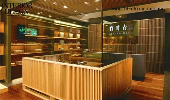 """在中国传统文化中,竹象征正直、高雅、纯洁、谦虚及有气节的君子形象,这种品质恰巧符合了竹叶青的企业文化及品牌气质,因此设计师在专卖店的整体设计中特别强调了""""竹""""的概念。专卖店从功能上划分为三个区域,即销售区、品茶区和收银区。首先,设计师将具有简约、时尚元素的木格栅应用在专卖店的大门设计中,创造出如竹林般的天然屏风,既能适当地遮挡室外过往人群的视线,又能将室内优雅、轻松的氛围巧妙地流露出去,吸引更多的路人走进专卖店。木格栅的设计同样还应用在品茶区的围栏隔断墙、顶部天花板以及收银台的背景"""