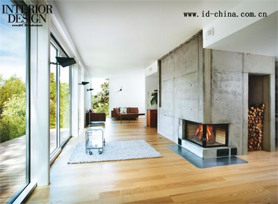 入口起居室与家庭起居室直接连通。作为传统家庭生活中的核心,家庭起居室占据了最好的景观位置。落地玻璃门直接通向建筑外的木质露台,与室内的木地板呼应,带来了连续的视觉效果;露台下的楼梯直接搭建在土坡上,两侧植被肆意生长,连同向阳侧温暖充足的阳光,带来了最惬意悠然的假日风光。起居室中心的壁炉不仅仅提供充足的暖气,更是一家人围炉闲话的核心,混凝土的质感为暖色调的空间带来了一丝凛然气氛,堆叠整齐的木炭配合跳跃的火焰与之形成有趣的对比。在凛冽的冬日,一家人在壁炉前悠赏窗外美景,岂不快哉!