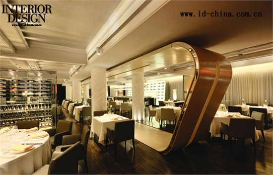 初到二层,会被一条狭小的走道引入,而后豁然开朗。正对着走道中轴的位置,设计重复了流动弯曲的浅色木质造型卷片,这个造型成为了室内设计的主要特征,好似横贯空间的飘带,在空间对称轴上,将餐厅大堂左右区域分隔开来,构成了室内造型的视觉焦点。红酒玻璃柜的介入,将右侧纵向空间再次进行区域分隔,使空间富有层次感和私密性。而酒柜玻璃的通透与酒水在灯光下的折射,成为了餐厅中的最佳装饰。与此相对,在左侧空间中,由切块锐角的白色石材造型和背景透光玻璃墙组合,构成酒吧区域的设计,成为卷片造型对岸的风景线。为强调两侧空间立面的
